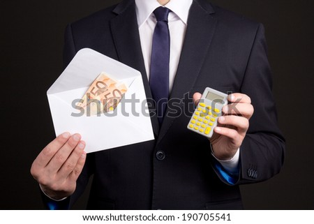 young business man holding envelope with money and calculator - stock photo