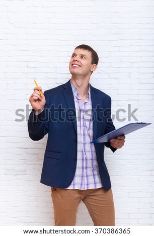 Young Business Man Holding Folder Pencil, Businessman Point To Copy Space Standing Over White Brick Wall - stock photo