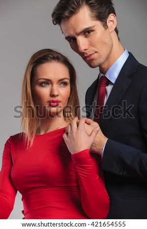 young business man holding hand on his wife's shoulder and looks at the camera - stock photo