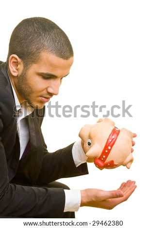 Young business man holding his hand under an empty piggy bank - stock photo