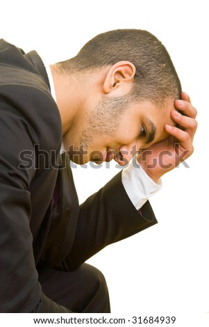 Young business man holding his head and thinking - stock photo