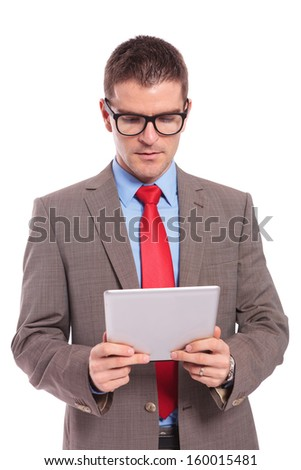 young business man holding his tablet and looking at it with a serious expression. on a white background