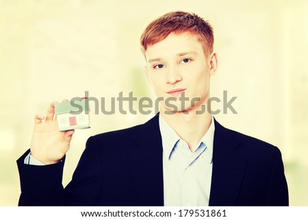 Young business man holding house model - real estate concept. - stock photo