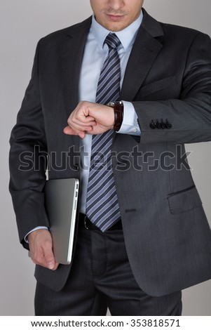 Young business man holding laptop and looking at his wristwatch checking the time. Time management and deadline concept - stock photo