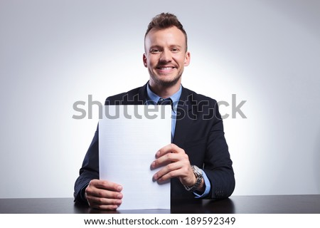 young business man holding some documents and smiling for the camera while seated at his office. on a light gray studio backgroud