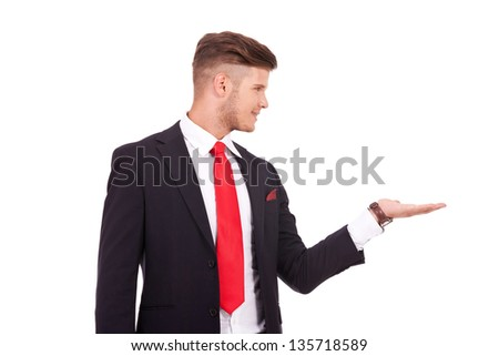 young business man holding something imaginary in his palm and looking at it while smiling. isolated on white background