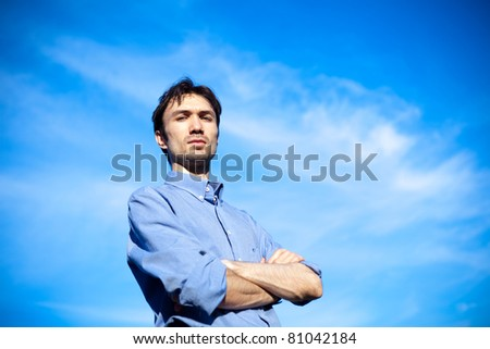 young business man in a blue shirt  against the blue sky. a symbol of leadership, success and freedom. - stock photo