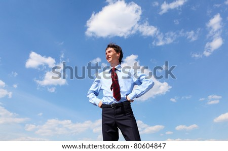young business man in a blue shirt and red tie against the blue sky. a symbol of leadership, success and freedom.