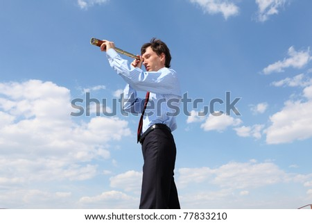 young business man in a blue shirt and red tie against the blue sky looks through a telescope. a symbol of leadership, success and freedom.