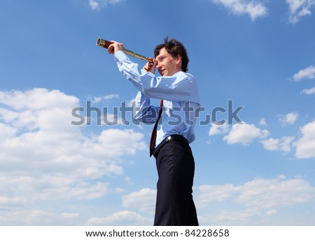 young business man in a blue shirt and red tie against the blue sky looks through a telescope. a symbol of leadership, success and freedom. - stock photo