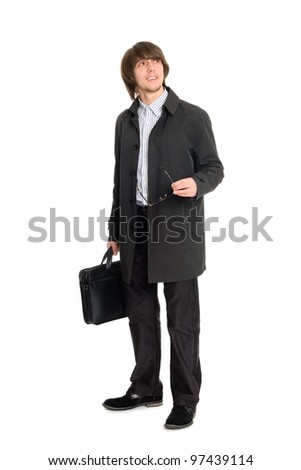 Young business man in a raincoat looking to the side.