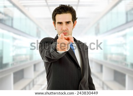 young business man in a suit pointing at the office