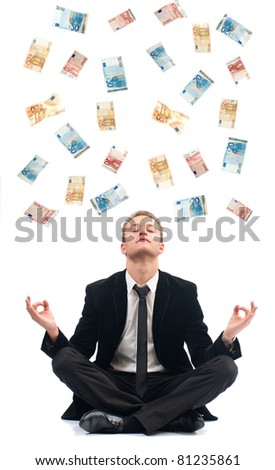 Young business man in a yoga position with a lot of bank note falling on him - stock photo