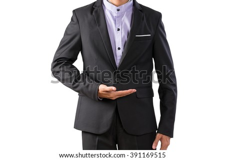Young business man in black suit showing hand copy space for your product advertising - stock photo