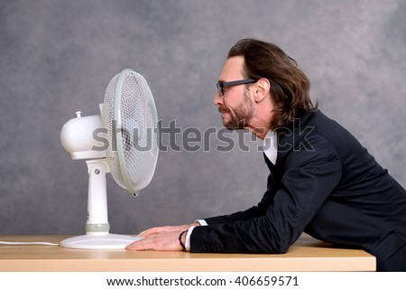 young business man in dark suit sitting in front of ventilator - stock photo