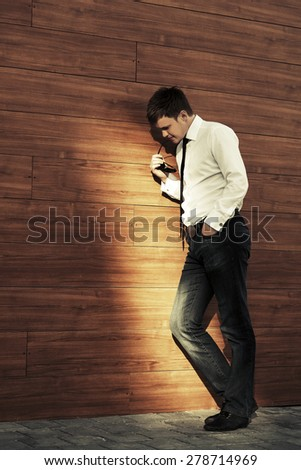 Young business man in depression standing at the wall - stock photo