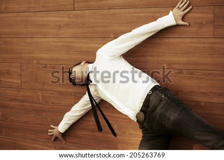 Young business man in despair lying on the floor - stock photo