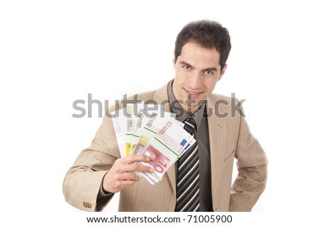 Young business man in light suit holding a wad of cash in hand and smiling at the camera, isolated on a white background.