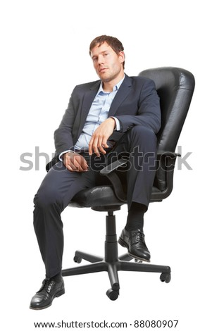 Young business man in office chair looking sceptical; isolated on white background