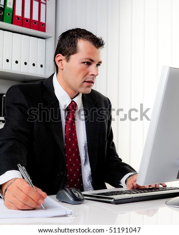 Young business man in office with computer - stock photo