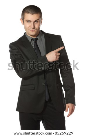 Young business man in suit pointing at copy space over white background - stock photo