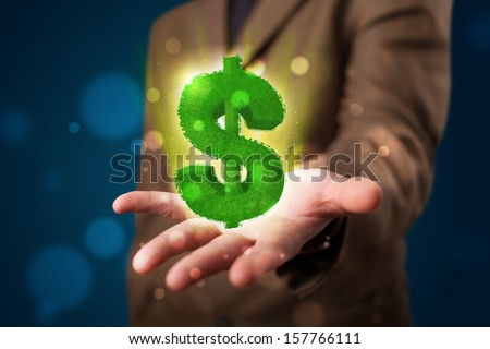 Young business man in suit presenting green glowing dollar sign - stock photo