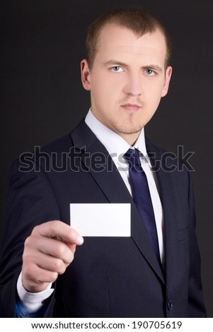 young business man in suit showing visiting card over grey background - stock photo