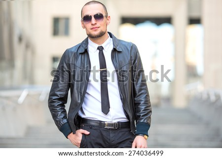 Young business man in sunglasses against the backdrop of the building business offices. Handsome modern man with sunglasses. Business man with sunglasses on the background of the business center.