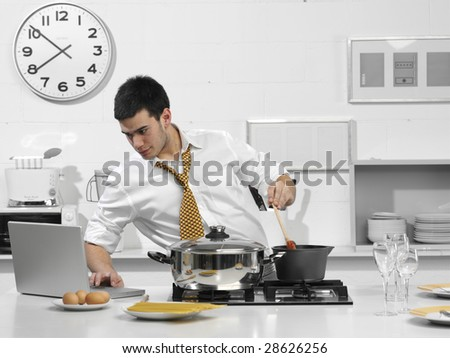 young business man in the kitchen with computer - stock photo