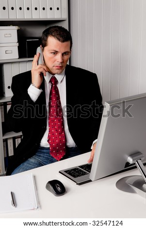 Young business man in the office with a telephone - stock photo