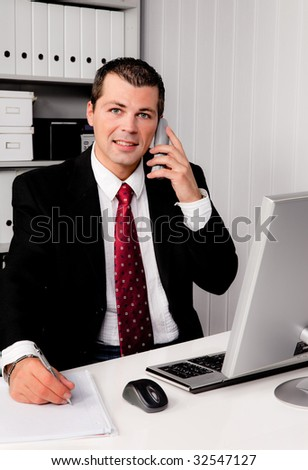 Young business man in the office with a telephone