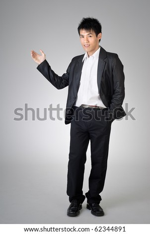 Young business man introduced over studio gray background. - stock photo