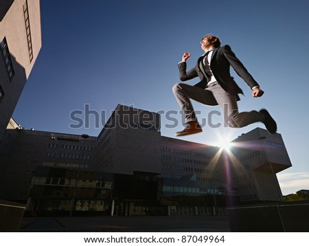 young business man jumping for joy outdoors, with office buildings and sun in background. Horizontal shape, side view, copy space - stock photo