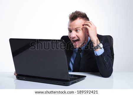 young business man laughing surprised while looking at his laptop. on a gray studio backgroud