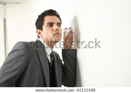 young business man listen at the wall with a glass - stock photo