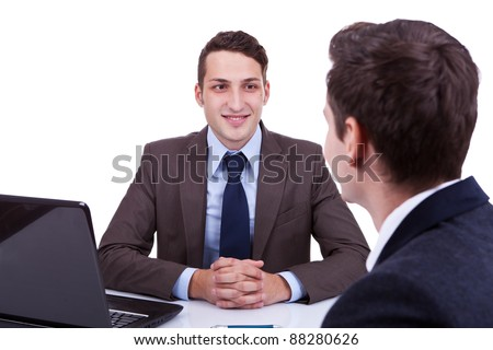 young business man listening at his desk to his employee, over white - stock photo