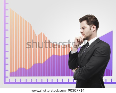 Young business man look at a graphs showing rise and fall in profits or earnings, falling orange. Financial diagrams. Rising arrow, representing business growth. On a gray background - stock photo