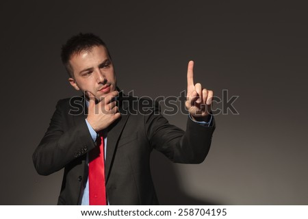 Young business man looking at his finger while thinking of something. He is holding his right hand to his chin. - stock photo