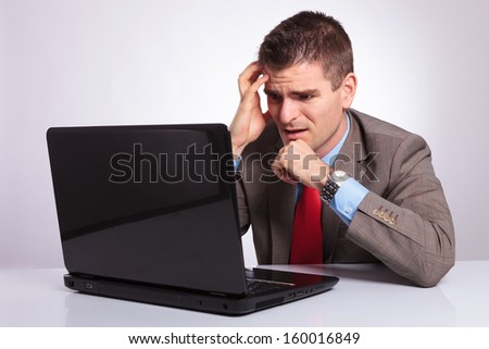young business man looking at his laptop with disappointment while holding his hands on his face. on gray background