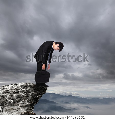 young business man looking depressed from work over danger precipice on the mountain, concept for business, asian people - stock photo