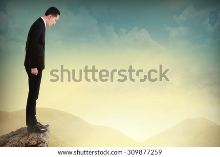 Young business man looking down the cliff want to suicide - stock photo
