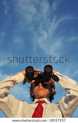 Young business man looking through binocular, low angle view - stock photo