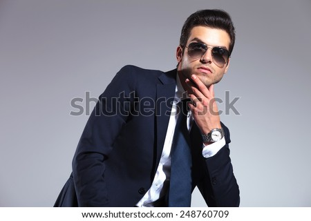 Young business man looking up while holding his hand to his chin, thinking of something. - stock photo