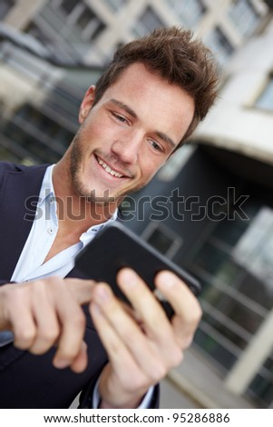 Young business man navigating in urban city with smartphone - stock photo