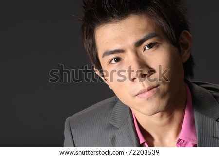 Young business man of Asian, closeup portrait on dark background. - stock photo