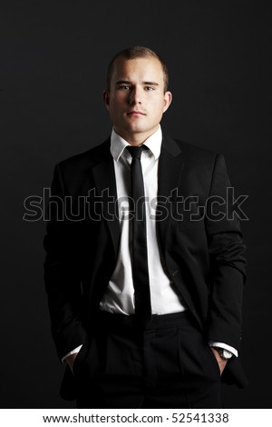 Young business man on black background looking seriously - stock photo