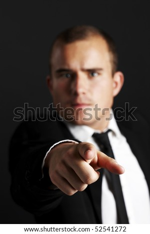 Young business man on black background pointing - stock photo