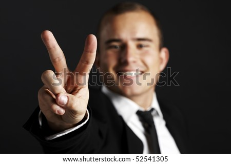 Young business man on black background shows the peace sign - stock photo