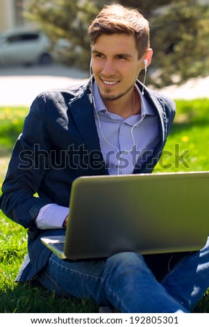 young business man on the grass. fashion style. talking skype. outdoor. summer