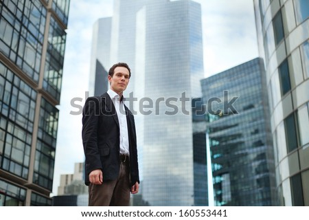 young business man on the office buildings background - stock photo